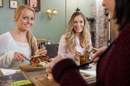 night out: Female Friends Eating Meal Together In Restaurant