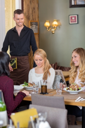 Female Friends With Food On Table While Waiter Holding Menu photo