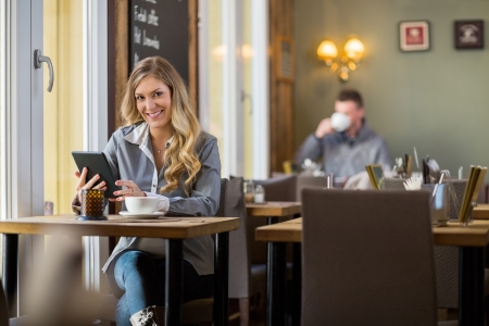 scandinavian people: Pregnant Woman Using Digital Tablet In Coffeeshop