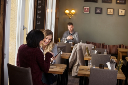 cafe shop: Female Friends Using Digital Tablet With Man In Background Stock Photo