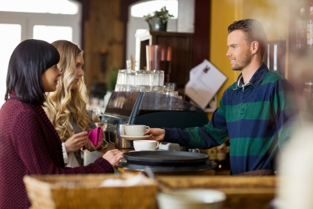 Bartender Serving Coffee To Women photo