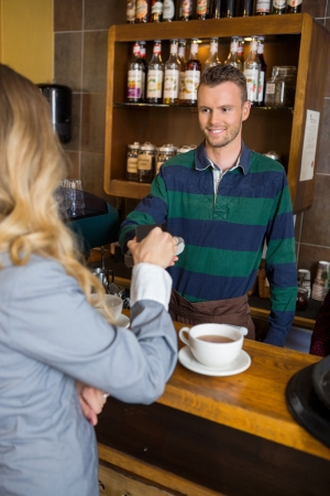 technology transaction: Bartender Holding Card-Reader While Woman Making Payment Through