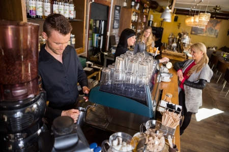 coffee machine: Bartender Working At Counter While Female Colleague Serving Coff