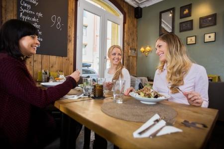socializando: Las mujeres que tienen comida en el restaurante Foto de archivo