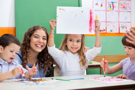 Teacher With Girl Showing Drawing At Desk Stock Photo
