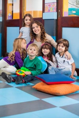 maestra preescolar: Profesor Y Estudiantes Sentado en el suelo en sala de clase Foto de archivo