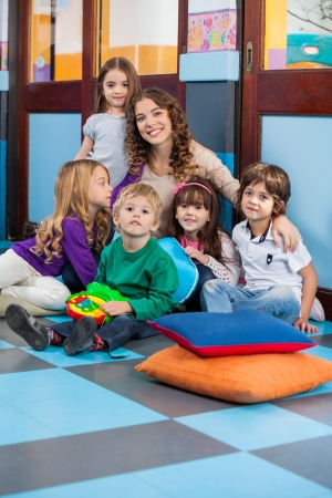 daycare: Teacher And Students Sitting On Floor In Classroom