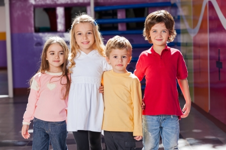 playhouse: Children Standing Arms Around In Kindergarten Stock Photo