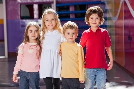 kinder: Los ni�os que colocan los brazos alrededor en Kindergarten