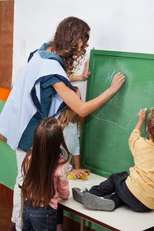 Teacher And Students Writing On Chalkboard In Classroom photo