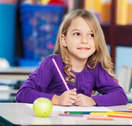niños en la escuela: Muchacha pensativa con Sketch lápiz y papel en el aula