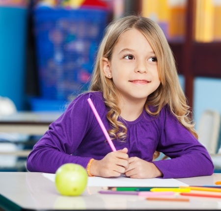 Promyšlený Girl With skici tužkou a papírem v učebně