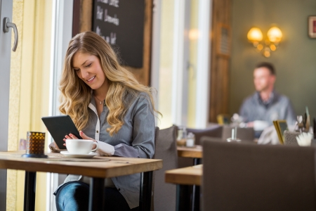 women coffee: Woman Using Digital Tablet At Table Stock Photo