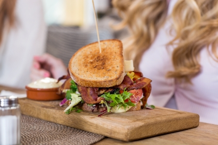 Sandwich On Wooden Plate With Women In Background Stock Photo - 20170031