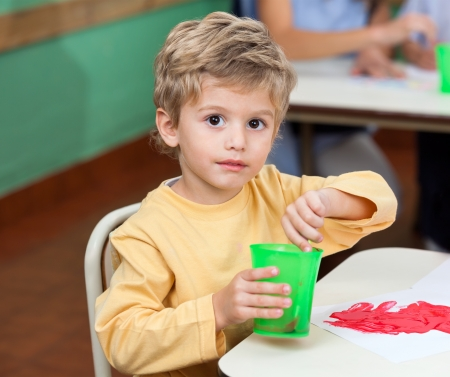Little Boy Washing Paintbrush In Glass Stock Photo - 19985908