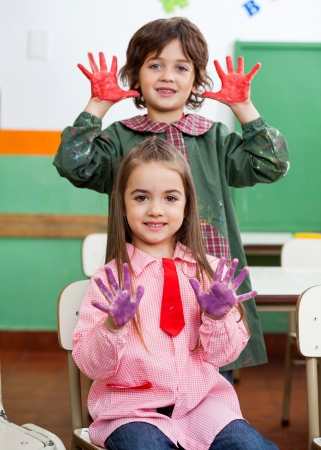 Boy And Girl Showing Colored Hands In Classroom Stock Photo - 19985945