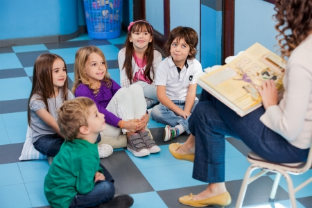 daycare: Teacher Reading Story Book To Children Stock Photo