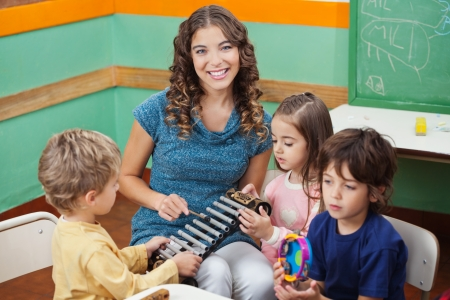 kindergarten toys: Teacher Playing Xylophone With Students In Preschool Stock Photo