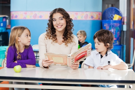 Teacher Holding Book With Children At Desk photo