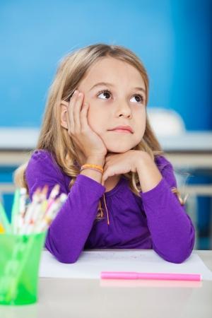 bambini pensierosi: Ragazza con la mano sul mento guardando lontano nel Class