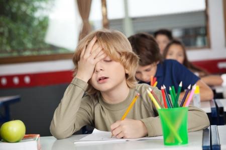 escuela primaria: Colegial cansado que se sienta en el escritorio en el aula Foto de archivo