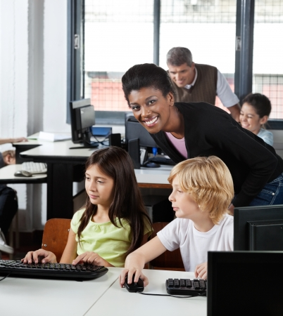 Female Teacher With Students At Desk Stock Photo - 20198946