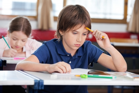 Thoughtful Schoolboy Sitting At Desk Stock Photo