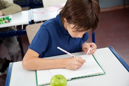 Schoolboy Copying From Cheat Sheet During Examination Stock Photo