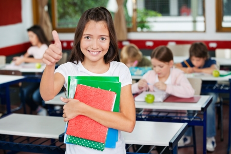 Schoolgirl Gesturing Thumbs Up While Holding Books photo
