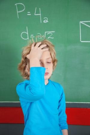 Sad Schoolboy Standing By Board In Classroom photo