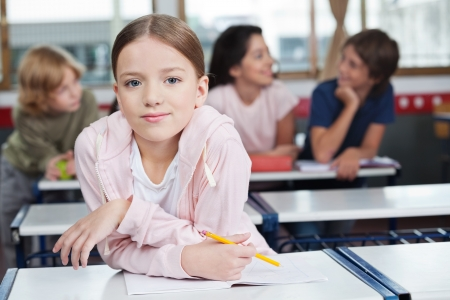 class room: Schoolgirl Leaning On Desk With Students In Background