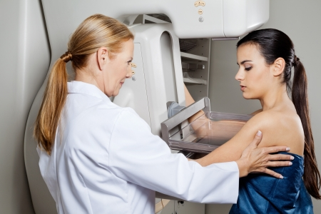 cancer x ray: Doctor Assisting Patient Undergoing Mammogram Stock Photo