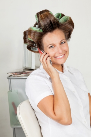 Happy Woman With Hair Curlers On Call photo