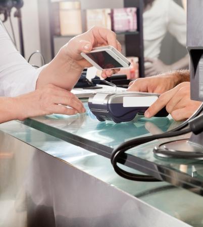 poblíž: Zákazník placení Mobilephone pomocí NFC Reklamní fotografie
