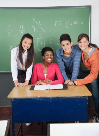 Teacher With Teenage Students At Desk In Classroom photo