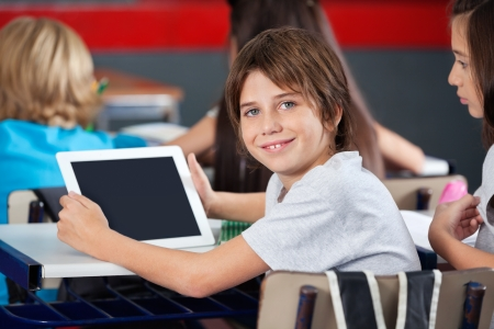 primary education: Cute Schoolboy Holding Digital Tablet In Classroom