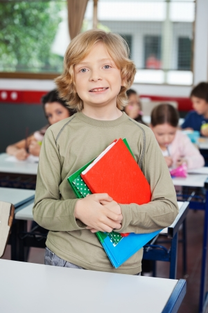 Schoolboy With Books Standing At Desk photo