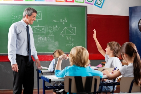 class room: Professor Looking At Schoolboy Raising Hand