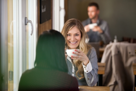 scandinavian people: Young Woman With Friend Having Coffee At Cafe Stock Photo