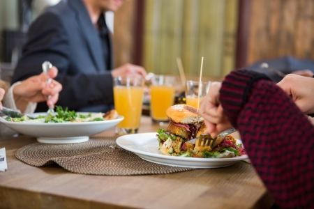 coffeeshop: Young Woman Having Burger With Colleagues At Cafe Stock Photo