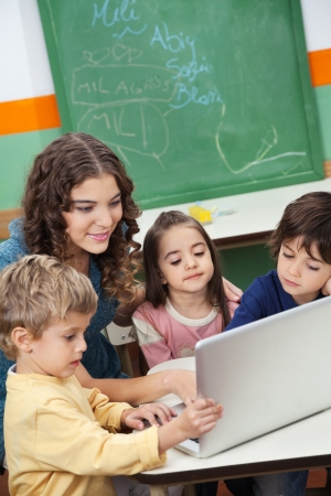 Teacher And Students Using Laptop In Class photo