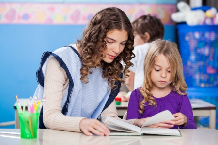 Teacher And Little Girl Reading Book In Classroom photo