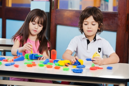Children Playing With Construction Blocks At Desk photo