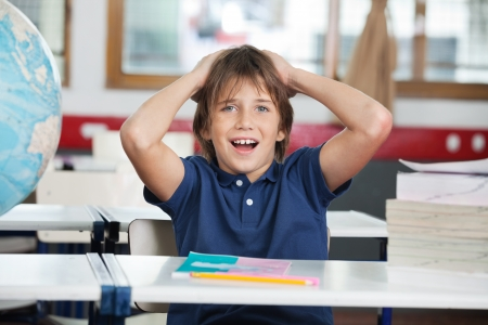 Shocked Little Boy With Globe And Books At Desk photo