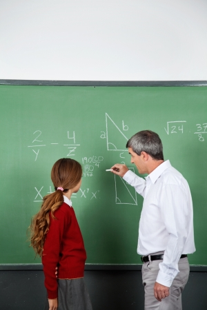 Teacher and student at blackboard photo