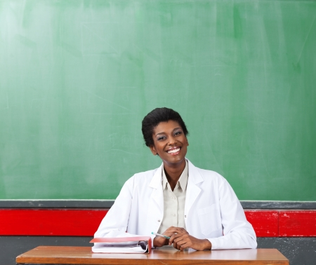 Happy Female Teacher Sitting At Desk In Classroom photo