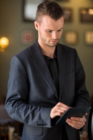 Businessman Using Digital Tablet At Cafe photo
