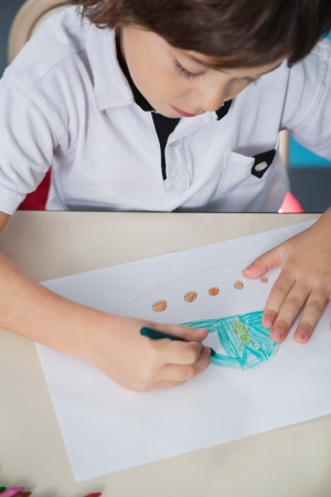 Boy Drawing With Color Pencil In Classroom photo