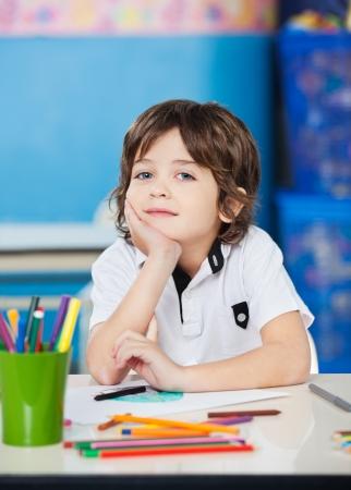 Boy Sitting With Hand On Chin In Drawing Class 版權商用圖片