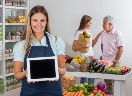 tiendas de comida: Vendedora Viendo Tablet con los clientes en el fondo